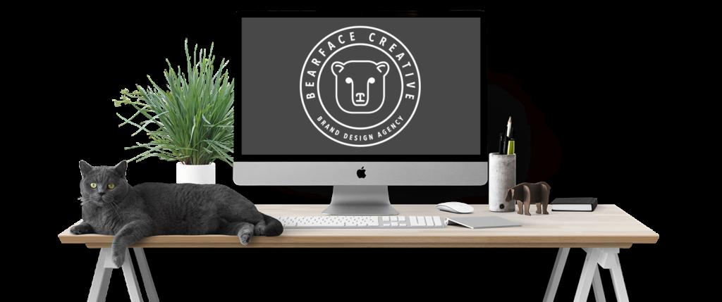 Cat laying on desktop, showing BearFace Creative Logo